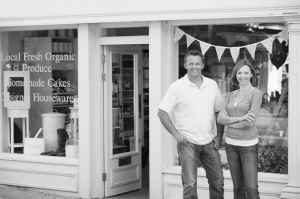 Couple standing in front of their store